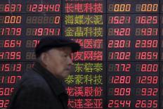 Un inversor camina junto a un tablero electrónico que muestra información bursátil, en una correduría en Shanghái, China, 14 de marzo de 2016. Las acciones de China cerraron al alza el miércoles, cuando la sesión anual del Parlamento llegó a su fin. REUTERS/Aly Song