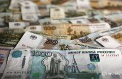 Рублевые банкноты различного достоинства. Рубль обновляет максимумы в паре с долларом после заседания ФРС США, итоги которого спровоцировали падение американской валюты и бурный рост на сырьевых и развивающихся рынках в надежде на сохранение относительно дешевого долларового фондирования высокорискованных операций. REUTERS/Kacper Pempel
