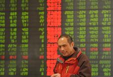 Un inversor frente a un tablero electrónico que muestra información bursátil, en una correduría en Fuyang, China. 29 de febrero de 2016. Las acciones chinas subieron más de un 1 por ciento el jueves, luego de que la búsqueda de ofertas en los valores tecnológicos contrarrestó la debilidad en los papeles financieros. REUTERS/China Daily