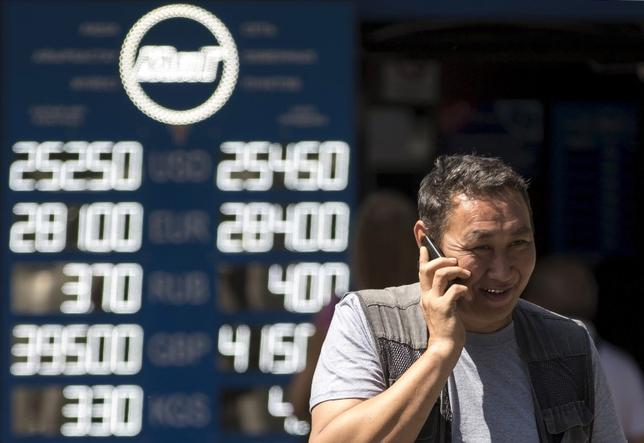 A man talks on his mobile phone as he walks past a board showing currency exchange rates in Almaty, Kazakhstan, August 20, 2015.  REUTERS/Pavel Mikheyev