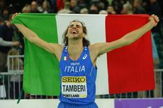 Gold medalist Gianmarco Tamberi of Italy celebrates with his country's flag after the men's high jump competition at the IAAF World Indoor Athletics Championships in Portland, Oregon March 19, 2016.  REUTERS/Mike Blake