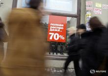 People walk past a shoe retailer advertising a sale in central St Petersburg February 26, 2009. Russia's economic outlook darkened with a government forecast for a 2.2 percent contraction adding to a batch of gloomy data releases to put pressure on the rouble and stocks.  REUTERS/Alexander Demianchuk (RUSSIA) - RTXC3SB