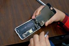 Un hombre intenta reparar un iPhone, en una tienda en Nueva York, 17 de febrero de 2016. La empresa israelí Cellebrite, un proveedor de software forense móvil, está ayudando a la Oficina Federal de Investigaciones de Estados Unidos (FBI) en su intento para desbloquear un iPhone usado por uno de los atacantes de San Bernardino, California, informó el miércoles el diario Yedioth Ahronoth. REUTERS/Eduardo Munoz