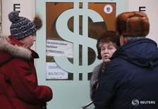 Люди у пункта обмена валюты в Москве 17 декабря 2014 года. Рубль в минусе на торгах среды - верх взяла текущая отрицательная динамика нефти, но с ней значительную часть дня пытались бороться экспортеры, продавая в умеренных количествах валютную выручку к пику налогового периода. REUTERS/Maxim Zmeyev