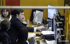 Трейдеры работают на фондовой бирже в Москве. Снижение российского  фондового рынка усилилось во второй половине торгов четверга вместе с коррекцией нефтяных котировок, и биржевые индексы готовятся завершить в минусе вторую сессию. REUTERS/Denis Sinyakov