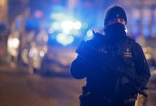 Сотрудник полиции принимает участие в операции в брюссельском районе Схарбек  25 марта 2016 года. Бельгийская полиция арестовала шесть человек, подозреваемых в причастности ко взрывам в аэропорту и метро Брюсселя, а французские власти объявили, что им удалось сорвать план новых атак экстремистов. REUTERS/Vincent Kessler