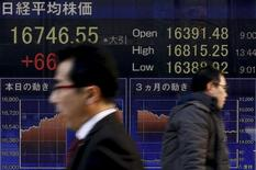 Personas caminan junto a un tablero electrónico que muestra el índice Nikkei, afuera de una correduría en Tokio, Japón, 2 de marzo de 2016. Las acciones japonesas subieron el viernes luego de que la debilidad del yen aumentó la confianza en el mercado. REUTERS/Thomas Peter