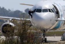 Человек выбирается из пилотской кабины захваченного египетского Airbus A320 в аэропорту кипрской Ларнаки 29 марта 2016 года. Пояс смертника, которым угрожал угонщик приземлившегося на Кипре самолета EgyptAir оказался муляжом, сообщили власти. Захватчик после переговоров позволил пассажирам покинуть самолет, а затем сдался. REUTERS/Yiannis Kourtoglou