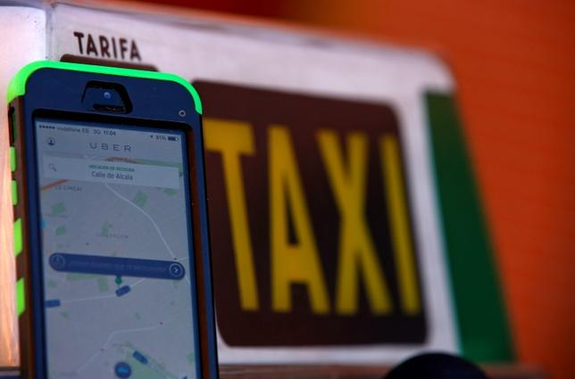 A car-sharing service app Uber on a smartphone next to a taxi sign is seen in this photo illustration taken in Madrid on December 10, 2014.   REUTERS/Sergio Perez