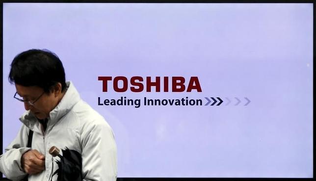 A man walks past a Toshiba Corp logo displayed on one of its television sets in Tokyo, Japan, November 26, 2015.  REUTERS/Toru Hanai