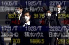 Peatones que usan máscaras se reflejan en un tablero electrónico que muestra los índices bursátiles de varios países, en Tokio, Japón, 26 de febrero de 2016. Las bolsas de Asia subían el miércoles en momentos en que los mercados recortaban sus expectativas sobre cuán rápido y en qué medida podrían aumentar las tasas de interés en Estados Unidos este año, lo que debilitaba al dólar. REUTERS/Yuya Shino