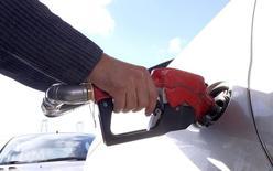 Человек заправляет бензином автомобиль на автозаправочной станции в Тегеране. Добыча нефти в странах ОПЕК выросла в марте, согласно данным исследования Рейтер, благодаря увеличению поставок из Ирана после снятия санкций, а также почти рекордному объёму экспорта из южного Ирака, что в совокупности покрыло снижение объёмов производства в более мелких экспортёрах. REUTERS/Raheb Homavandi/TIMA