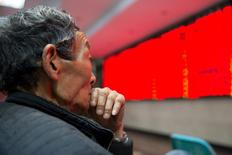 Un inversor mira una pantalla electrónica que muestra información bursátil, en una correduría en Nanjing, China. 30 de marzo de 2016. Las acciones chinas extendieron sus ganancias el jueves tras un salto de un 2 por ciento en la sesión anterior, debido a que los inversores seguían animados por la perspectiva de que las tasas de interés de Estados Unidos subirán a un ritmo más lento. REUTERS/China Daily