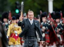 Olympic gold medal cyclist Chris Hoy carries the Commonwealth Games Baton along The Mall to Buckingham Palace in London October 9, 2013. REUTERS/Stefan Wermuth