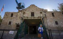 A woman walks past as men use a lift to repair and restore stonework along the curved facade of the Alamo in San Antonio, Texas in this October 26, 2015 file photo.   Preservation Design Partnership, a Philadelphia-based firm that worked in the refurbishment of landmarks including Independence Hall, the U.S. Supreme Court Building, and the Virginia State Capitol was named March 31, 2016, to head the effort to renovate the Alamo in San Antonio.  REUTERS/Adrees Latif/Files