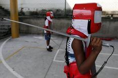 """A child, from Municipal school Parana, poses during the project """"Fencing School"""" in Rio de Janeiro, Brazil, March 30, 2016.  REUTERS/Sergio Moraes"""
