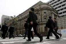 Люди проходят мимо здания Банка Японии в Токио 23 марта 2016 года. Долгосрочные инфляционные ожидания японских компаний ослабли в марте по сравнению с показателями трёхмесячной давности, свидетельствуют результаты исследования центробанка. Это стало признаком того, что решение о переходе к отрицательным ставкам в январе не убедило фирмы в постепенном росте цен. REUTERS/Toru Hanai
