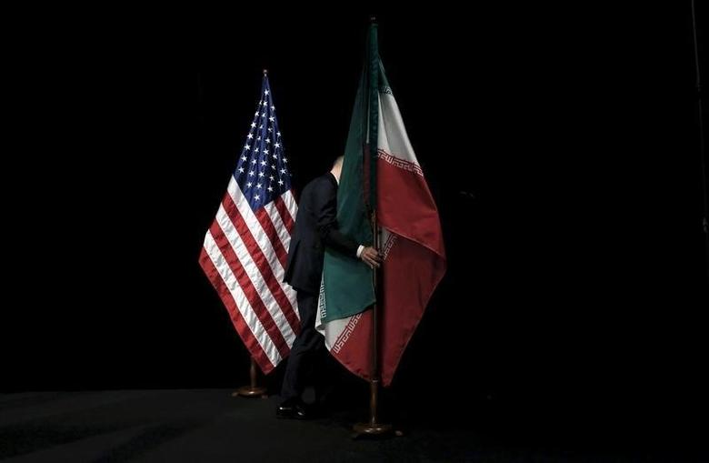 A staff member removes the Iranian flag from the stage during the Iran nuclear talks in Vienna, Austria July 14, 2015. REUTERS/Carlos Barria