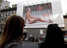 En la imagen de archivo, dos mujeres observan un cartel publicitario con la imagen de una mujer desnuda escandalosamente delgada en Milán, el 24 de septiembre de 2007.  Una ley destinada a reducir los trastornos alimentarios en los modelos ha superado su primer obstáculo legislativo en California, tras los esfuerzos de varios países para luchar contra la extrema delgadez. REUTERS/Stefano Rellandini (ITALIA)