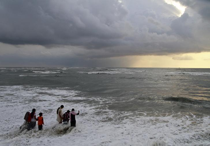 Beachgoers walk in the waters at Fort Kochi beach as clouds hover over the Arabian Sea in Kerala May 23, 2013. REUTERS/Sivaram V/Files