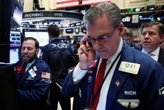 Трейдеры на торгах Нью-Йоркской фондовой биржи 12 апреля 2016 года. Уолл-стрит завершила торги четверга малоподвижной динамикой после двух дней сильного роста, поскольку инвесторы анализировали результаты квартальных отчётов нескольких крупных банков, в то время как финансовый сектор продолжил восстанавливаться. REUTERS/Lucas Jackson