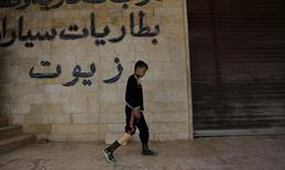 A boy with an amputated leg walks using an artificial limb in the rebel-controlled area of Maaret al-Numan town in Idlib province, Syria March 20, 2016. REUTERS/Khalil Ashawi