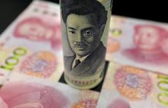 Банкнота в 1000 иен на фоне китайских юаней.  Доллар упал на 0,5 процента к иене в пятницу из-за падения цен на нефть в преддверии встречи основных нефтедобывающих стран в Дохе, что снизило аппетит инвесторов к риску, направив внимание в сторону традиционно надёжной японской валюты. REUTERS/Jason Lee