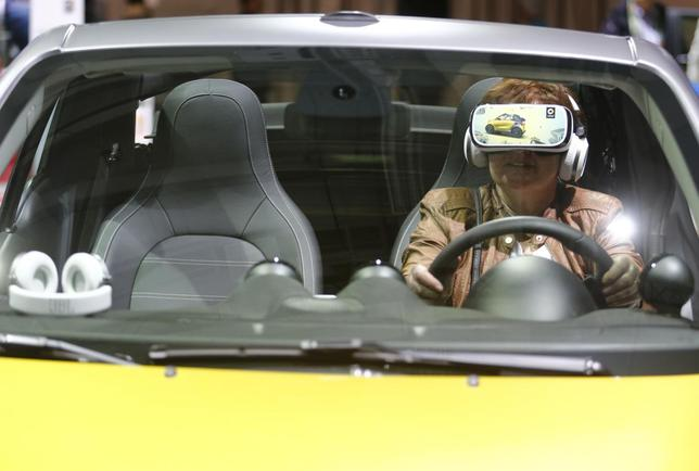 A woman uses virtual reality goggles while sitting in a 'smart fortwo cabrio' car prior to the Daimler annual shareholder meeting in Berlin, Germany, April 6, 2016.   REUTERS/Hannibal Hanschke
