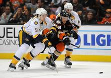 April 15, 2016; Anaheim, CA, USA; Anaheim Ducks left wing Jamie McGinn (88) moves the puck against the defense of Nashville Predators center Filip Forsberg (9) and defenseman Shea Weber (6) during the second period in game one of the first round of the 2016 Stanley Cup Playoffs at Honda Center. Mandatory Credit: Gary A. Vasquez-USA TODAY Sports