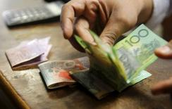 Сотрудник обменного пункта в Каире пересчитывает австралийские доллары.  Сырьевые валюты, такие как австралийский и канадский доллар, отошли от недавних максимумов в среду, поскольку рост цен на нефть приостановился после окончания забастовки нефтяников в Кувейте. REUTERS/Amr Abdallah Dalsh