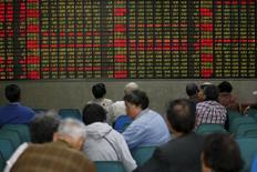 Inversores miran un panel electrónico que muestra información bursátil, en una correduría en Shanghái, China. 21 de abril de 2016. Las acciones chinas cerraron a la baja el jueves luego de que una toma de ganancias en los papeles financieros y de manufactura contrarrestaron unos avances iniciales de los valores ligados a las materias primas. REUTERS/Aly Song