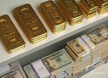 Слитки золота и долларовые купюры в сейфе банка в Вене 21 июля 2009 года. Золотовалютные резервы РФ на конец прошлой недели составили $386,2 миллиарда, снизившись с предыдущего значения $387,9 миллиарда, которое было максимальным с 26 декабря 2014 года. REUTERS/Heinz-Peter Bader