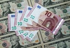 Доллары и евро в Вене. Евро снижается по отношению к доллару США в ходе торгов четверга, поскольку трейдеры постепенно переключают внимание с сегодняшнего заседания Европейского центробанка и оценивают вероятность ужесточения денежно-кредитной политики ФРС, заседание которого состоится на следующей неделе.   REUTERS/Heinz-Peter Bader