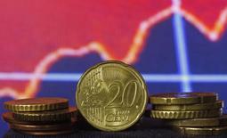 Евроцены на фоне графика движения акций.  Евро стабилизировался в пятницу после волатильных торгов ночью, поскольку по итогам заседания Европейского центробанка рынки оказались между твердой позицией регулятора с одной стороны и ожиданиями новых мер стимулирования - с другой. REUTERS/Dado Ruvic
