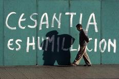 Foto de archivo de un hombre caminando junto a un grafiti con motivo de las altas tasas de cesantía, en el centro de Santiago. 11 de febrero de 2009. El desempleo en la capital chilena subió a un 9,4 por ciento en marzo, su mayor nivel interanual en seis años, en una señal de que el mercado laboral ya siente los efectos del bajo dinamismo económico, mostró el lunes un informe de una universidad. REUTERS/Ivan Alvarado
