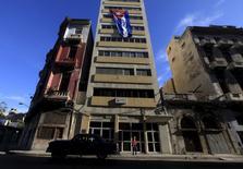 Una bandera cubana colgando de un edificio en La Habana, abr 24, 2016. Un grupo de acreedores formado para negociar con Cuba deuda en cesación de pagos ha comenzado las negociaciones con La Habana, dijo a Reuters el coordinador recientemente asignado del equipo, quien advirtió sobre la necesidad de acelerar el proceso.  REUTERS/Enrique de la Osa