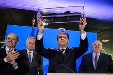 Le président François Hollande au siège de la DCNS à Paris, entouré (de gauche à droite) du ministre de la Défense Jean-Yves Le Drian, du chef de la diplomatie Jean-Marc Ayrault et du PDG des chantiers de construction navale Hervé Guillou. L'annonce mardi d'un contrat pour des sous-marins australiens est le fruit d'un an et demi de discussions en coulisses. /Photo prise le 26 avril 2016 /REUTERS/Christophe Petit-Tesson/Pool