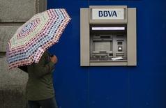BBVA experimentó una mejora de sus márgenes en el primer trimestre del año, aunque el beneficio neto se redujo a la mitad y los resultados se situaron por debajo de las previsiones de los analistas. En la imagen, una mujer con paraguas junto a un cajero de BBVA en Madrid, el 4 de abril de 2016. REUTERS/Andrea Comas