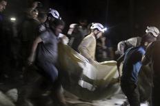 Сотрудники организации гражданской обороны несут жертву после авиаударов по полевому госпиталю в районе Алеппо.  Жертвами авиаударов по больнице в подконтрольном повстанцам районе сирийского Алеппо стали 20 человек, в том числе трое детей и единственный оставшийся в городе врач-педиатр, сообщил Наблюдательный совет по правам человека в Сирии в четверг. REUTERS/Abdalrhman Ismail