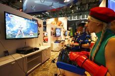 Женщины в костюмах персонажей Streetfighter играют в Playstation на выставке в Кёльне 5 августа 2015 года. Японский производитель электроники Sony Corp в четверг отчитался о наиболее значительной годовой операционной прибыли с 2007 финансового года, чему способствовало сокращение расходов в убыточном подразделении по выпуску смартфонов, а также высокий спрос на видеоигры для PlayStation 4. REUTERS/Kai Pfaffenbach