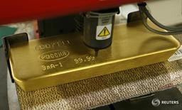 Машина гравирует слиток золота на заводе Красцветмет в Красноярске 27 февраля 2014 года. Золотовалютные резервы РФ на конец прошлой недели составили $388,6 миллиарда, и это максимальное значение с 26 декабря 2014 года, на которое они вышли с предыдущего значения $386,2 миллиарда в основном за счет переоценки валют и активов, помимо доллара США, входящих в структуру резервов. REUTERS/Ilya Naymushin