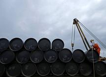 Un trabajador prepara barriles de petróleo para transportarlos, en Johor. 4 de febrero de 2015. Decenas de buques cisterna con crudo que aún no ha sido vendido se han estado acumulando en el mar en las últimas semanas, una situación que recuerda a la crisis del 2015, cuando la recuperación de los precios del petróleo fue aplastada por el incremento de los suministros físicos. REUTERS/Edgar Su/Files