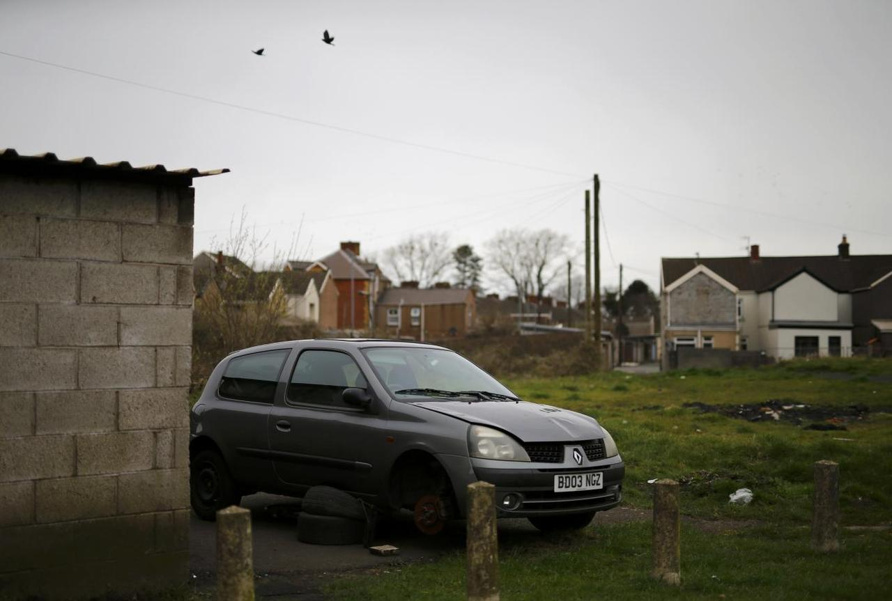 A broken car sits on a housing estate near the Tata steelworks in the town of Port Talbot, Wales, Britain April 1, 2016. REUTERS/Darren Staples
