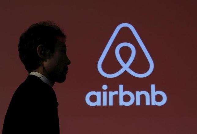 A man walks past a logo of Airbnb after a news conference in Tokyo, Japan, November 26, 2015. REUTERS/Yuya Shino