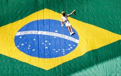 Brazilian firefighter Haudson Alves abseils with the Olympic flame as he attends the Olympic Flame torch relay at Mane Garrincha stadium in Brasilia, Brazil, May 3, 2016. REUTERS/Ueslei Marcelino