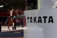 A logo of Takata Corp is seen with its display as people are reflected in a window at a showroom for vehicles in Tokyo, Japan in this November 6, 2015 file photo.   REUTERS/Toru Hanai/Files