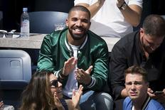 Musician Drake applauds as his image is displayed on the TV monitors during the Serena Williams, Roberta Vinci match at the U.S. Open Championships tennis tournament in New York, September 11, 2015. REUTERS/Carlo Allegri