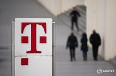 Люди проходят мимо логотипа Deutsche Telekom AG в Бонне 25 февраля 2016 года. Базовая прибыль Deutsche Telekom в первом квартале выросла благодаря успешной деятельности в США, что помогло компенсировать инвестиции в европейские сети, сообщила компания в среду. REUTERS/Wolfgang Rattay/File Photo
