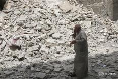 A man walks past the rubble of damaged buildings after an airstrike in the rebel held area of Aleppo's Baedeen district, Syria, May 3, 2016. REUTERS/Abdalrhman Ismail - RTX2CNTW