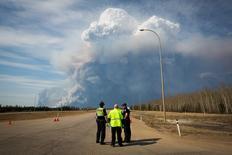 Облака дыма поднимаются над городом Форт-Мак-Марри в Канаде 4 мая 2016 года. Цены на нефть выросли в четверг в связи с масштабным лесным пожаром в Канаде, ставшим причиной сокращения добычи на нефтеносных песках, а также на фоне эскалации боевых действий в Ливии, ставящих под удар добычу чёрного золота в стране. REUTERS/Topher Seguin